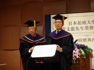名誉博士称号記を掲げる許文龍氏(左)と川名副学長